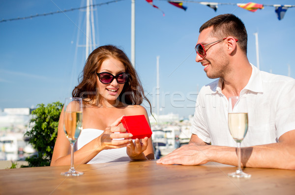 smiling couple with champagne and gift at cafe Stock photo © dolgachov