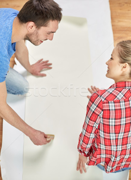 close up of couple smearing wallpaper with glue Stock photo © dolgachov