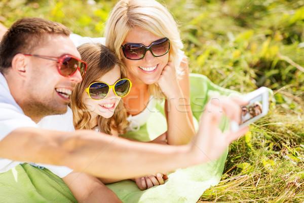 happy family with camera taking picture Stock photo © dolgachov