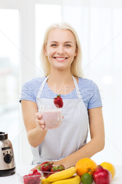 Stock photo: smiling woman holding glass of fruit shake at home