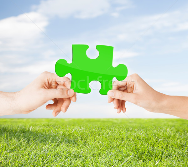hands with green puzzle over natural background Stock photo © dolgachov