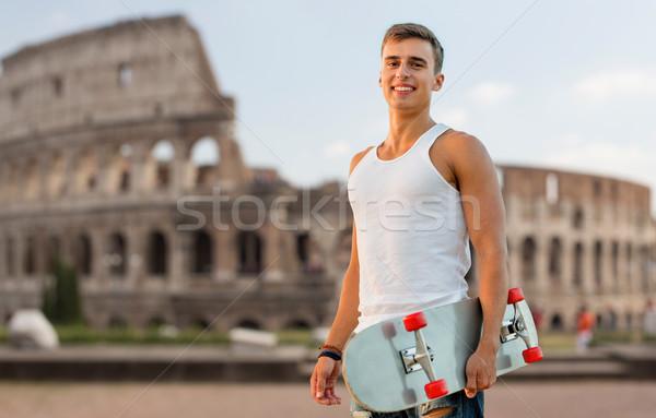 smiling teenage boy with skateboard over coliseum Stock photo © dolgachov
