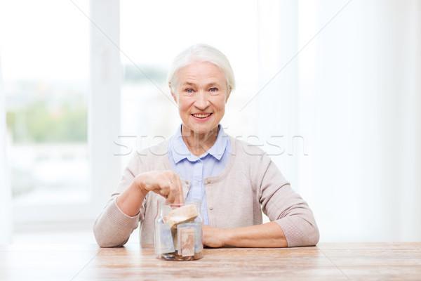 senior woman putting money into glass jar at home Stock photo © dolgachov