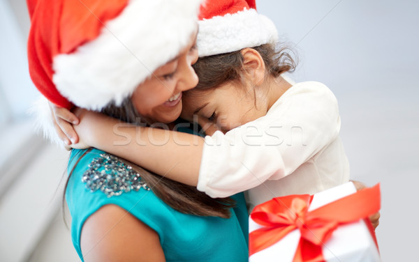 Stock photo: happy mother and little girl in santa hats at home