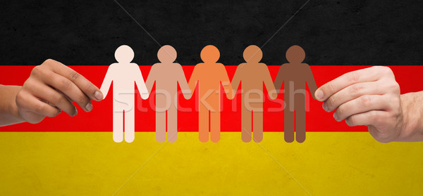 hands with paper people pictogram over german flag Stock photo © dolgachov