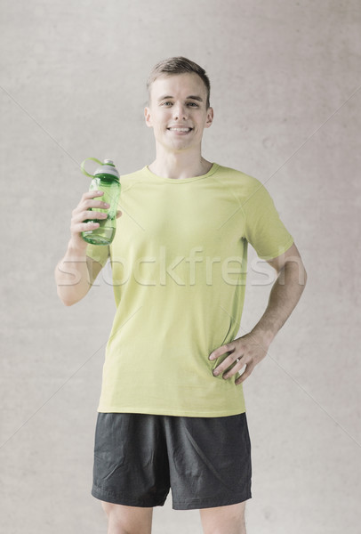 smiling man with bottle of water in gym Stock photo © dolgachov