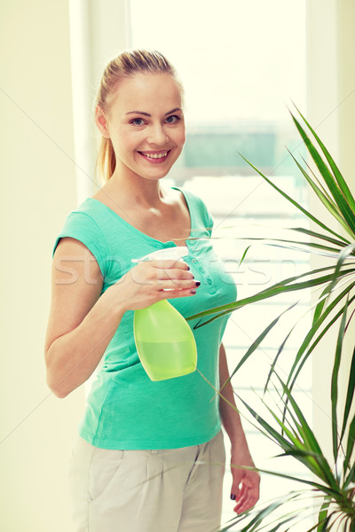 happy woman in spraying houseplants at home Stock photo © dolgachov