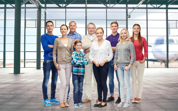 group of smiling people over airport terminal Stock photo © dolgachov