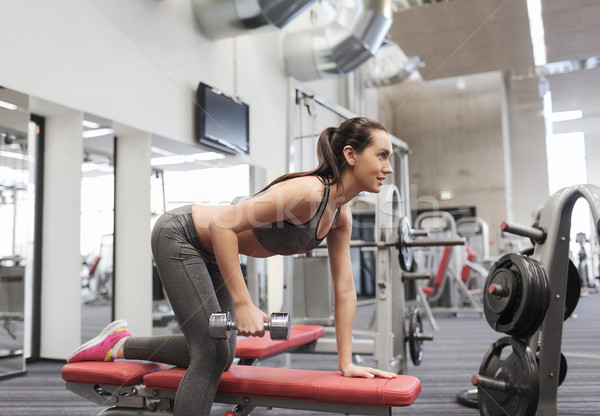 happy woman with dumbbell flexing muscles in gym Stock photo © dolgachov