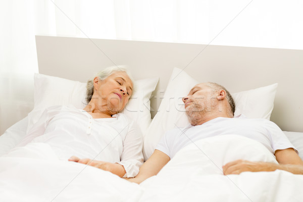 happy senior coupler lying in bad at home Stock photo © dolgachov