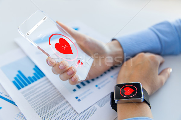 hands with heart icon on smartphone and smartwatch Stock photo © dolgachov