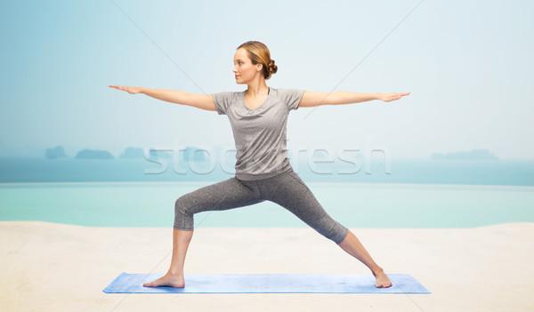 Stock photo: woman making yoga warrior pose on mat