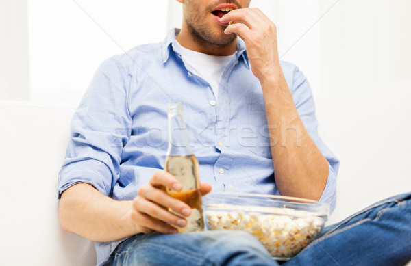 Stock photo: close up of man with popcorn and beer at home