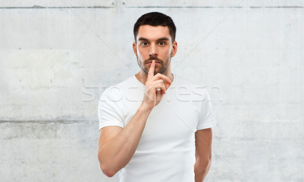 young man making hush sign over gray wall Stock photo © dolgachov