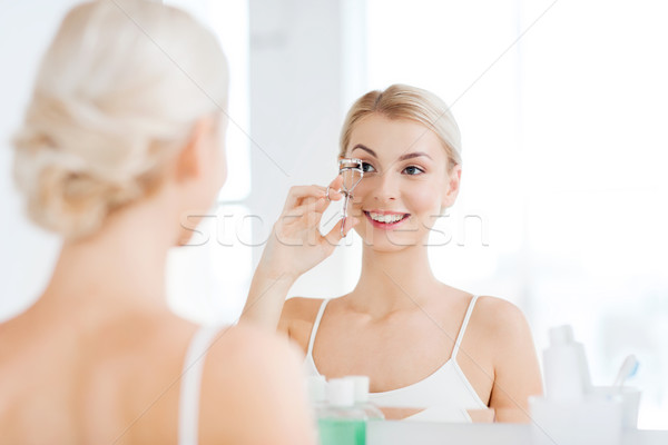 woman with curler curling eyelashes at bathroom Stock photo © dolgachov