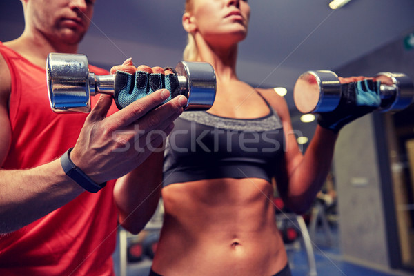 Stock photo: young couple with dumbbell flexing muscles in gym