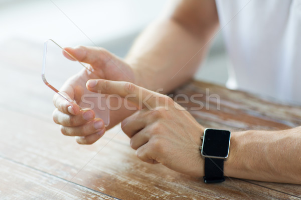 Stock photo: close up of hands with smart phone and watch