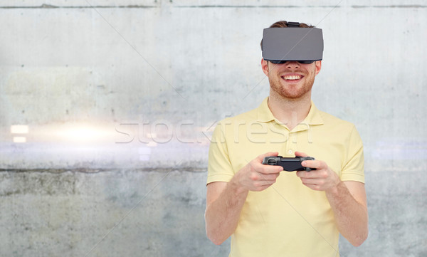 man in virtual reality headset and gamepad playing Stock photo © dolgachov