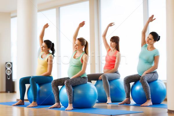happy pregnant women exercising on fitball in gym Stock photo © dolgachov