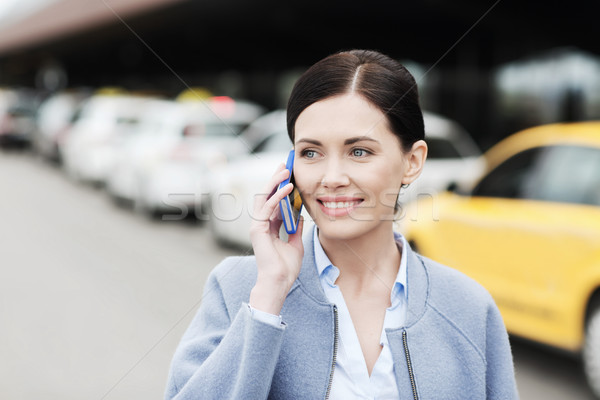 smiling woman with smartphone over taxi in city Stock photo © dolgachov