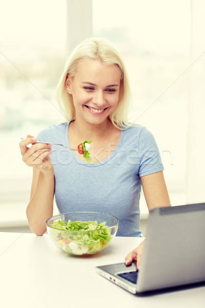 smiling woman with laptop eating salad at home Stock photo © dolgachov