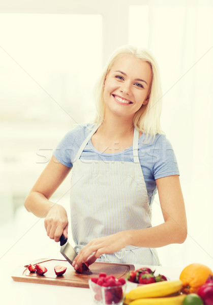 smiling young woman chopping fruits at home Stock photo © dolgachov