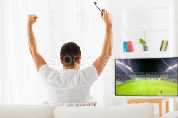 happy man watching football or soccer game on tv Stock photo © dolgachov