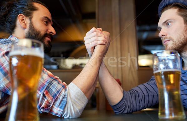 male friends arm wrestling at bar or pub Stock photo © dolgachov