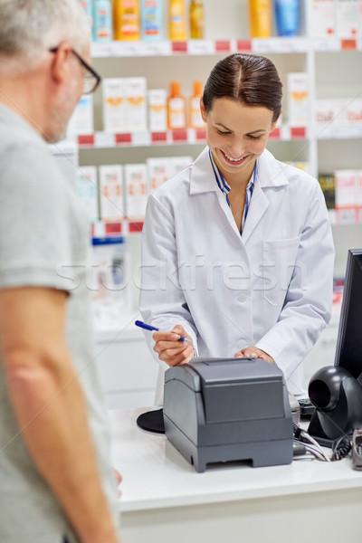 pharmacist writing check for customer at drugstore Stock photo © dolgachov