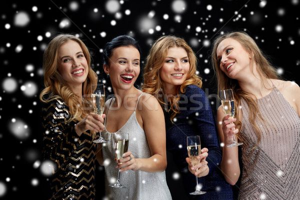 happy women with champagne glasses over black Stock photo © dolgachov