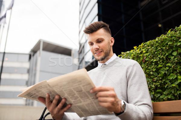 smiling man reading newspaper on city street bench Stock photo © dolgachov