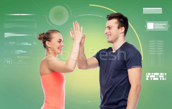 happy sportive man and woman making high five Stock photo © dolgachov
