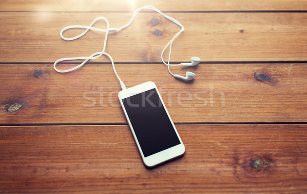 close up of blank smartphone and earphones on wood Stock photo © dolgachov