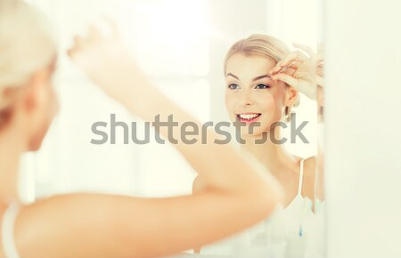 woman with tweezers tweezing eyebrow at bathroom Stock photo © dolgachov
