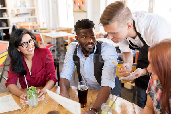 waiter and friends with menu and drinks at bar Stock photo © dolgachov