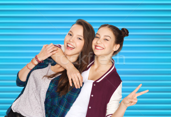 happy teenage girls hugging and showing peace sign Stock photo © dolgachov