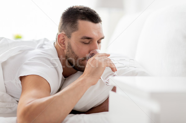 man in bed with glass of water drinking at home Stock photo © dolgachov