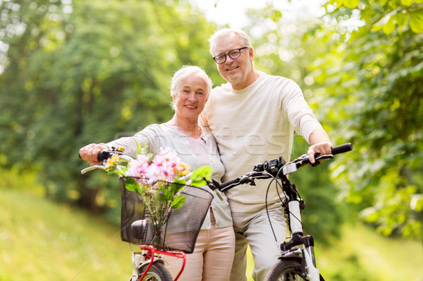 Stock photo: happy senior couple with bicycles at summer park