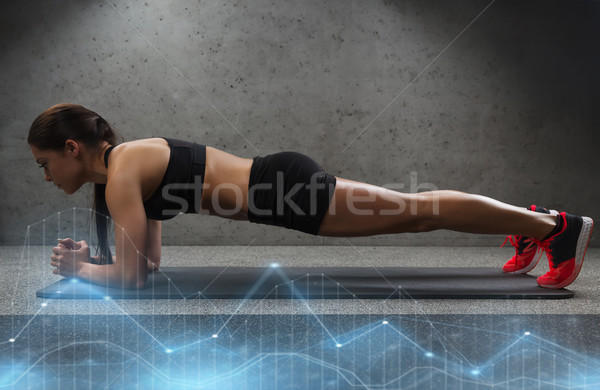 woman doing plank exercise on mat in gym Stock photo © dolgachov