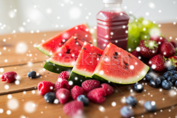 watermelon, bottle of fruit juice and berries Stock photo © dolgachov