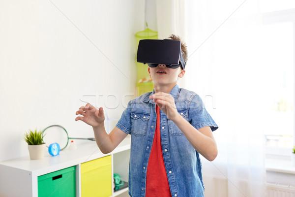 boy in virtual reality headset or 3d glasses Stock photo © dolgachov