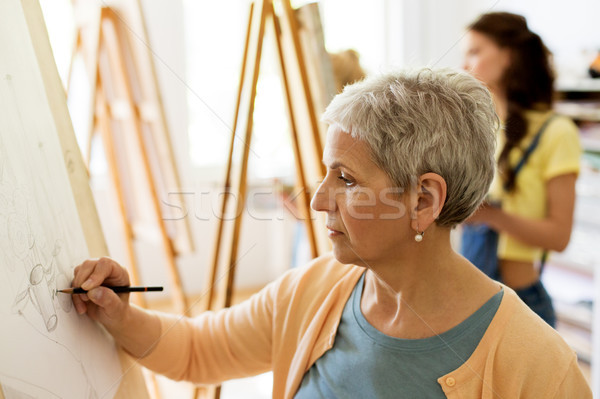 senior woman drawing on easel at art school studio Stock photo © dolgachov
