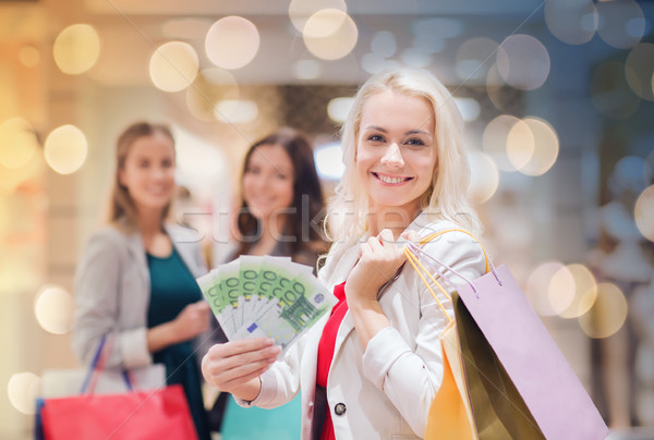 young women with shopping bags and money in mall Stock photo © dolgachov
