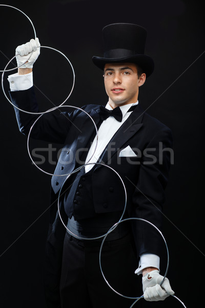 magician showing trick with linking rings Stock photo © dolgachov