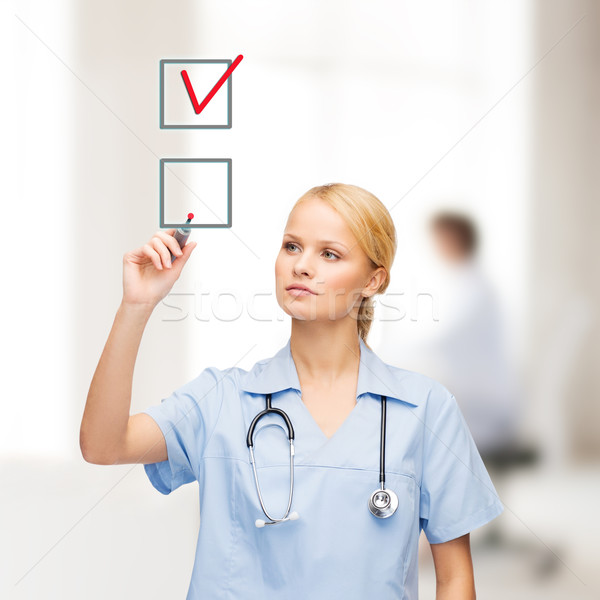 doctor or nurse with marker drawning red checkmark Stock photo © dolgachov