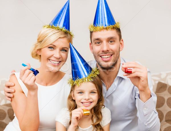 Mosolyog család kék sapkák fúj szívesség Stock fotó © dolgachov