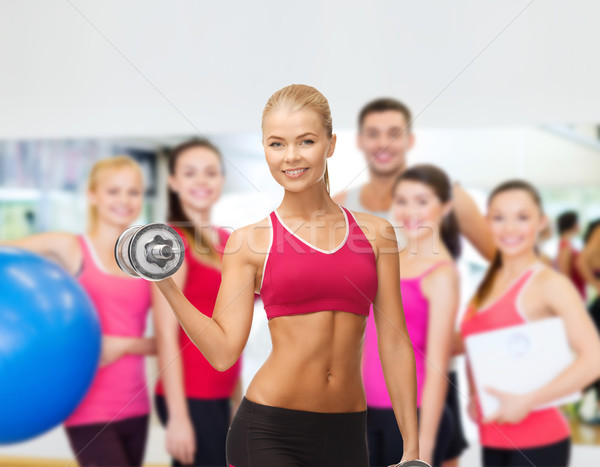 smiling woman with heavy steel dumbbells Stock photo © dolgachov