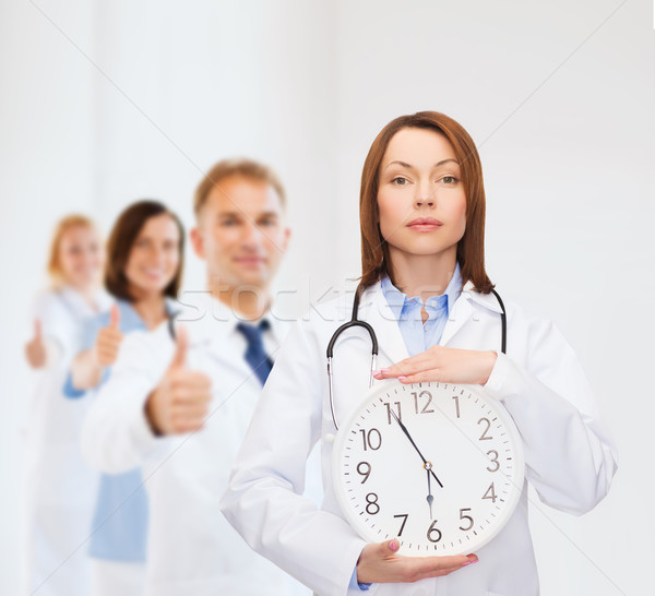 calm female doctor with wall clock Stock photo © dolgachov