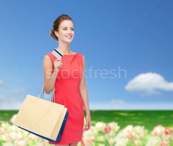 smiling woman with shopping bags and plastic card Stock photo © dolgachov