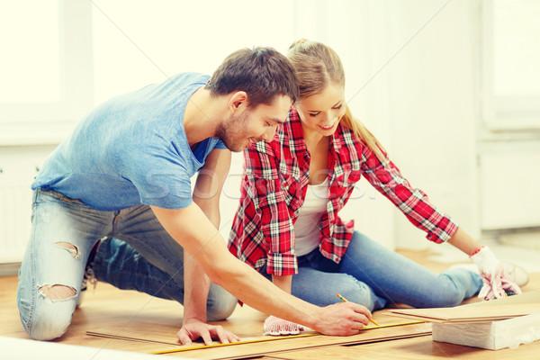 smiling couple measuring wood flooring Stock photo © dolgachov